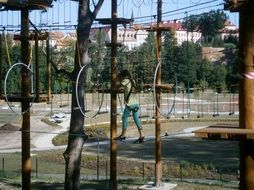 Girl is walking in the rope park