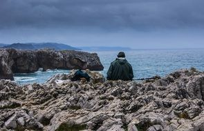 asturias fisherman sitting on the rocks