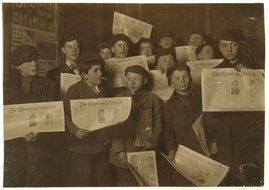 a group of boys with newspapers in their hands