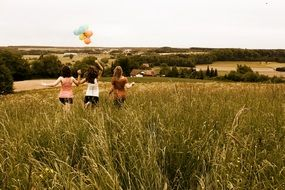 girls with balloons among the meadow