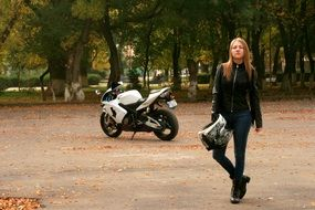 blonde girl in a leather jacket with a helmet in hand on the background of a motorcycle