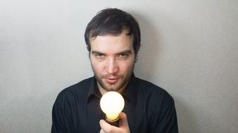 man with switched on lightbulb