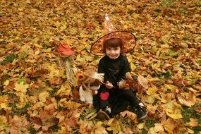 child dressed in carnival witch costume for Halloween on the background of autumn leaves