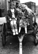 two child girls sitting on cart, vintage