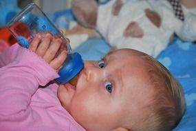 baby girl drinks from a bottle
