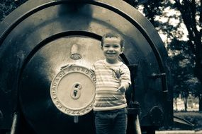 black and white photo of a child near a train