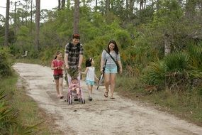 family is walking along a forest road