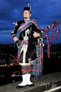 man in traditionally costume with bagpipes in view of night city, uk, scotland, edinburgh