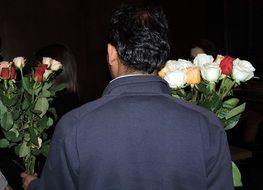 A man holds two bouquets of roses in his hands