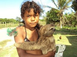 girl is holding a sloth