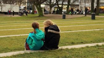 two girls sit together in park