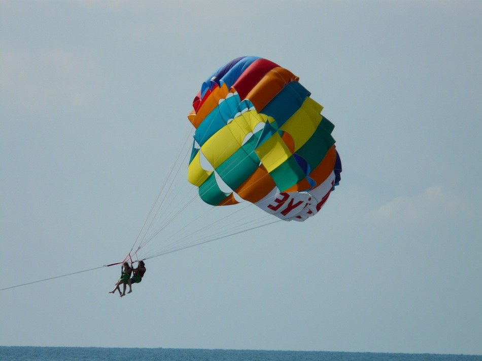 Two people on parachute hover over the water
