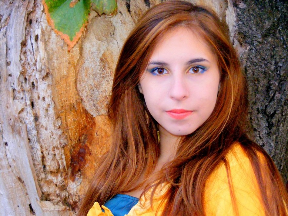 Girl with brown hair and beautiful eyes near a tree