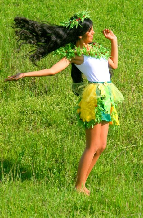 Girl with long black hair on a green meadow