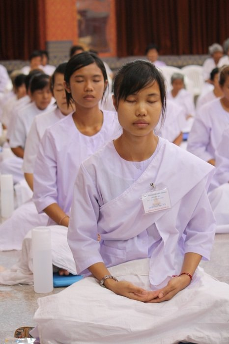 Women in white robes meditate