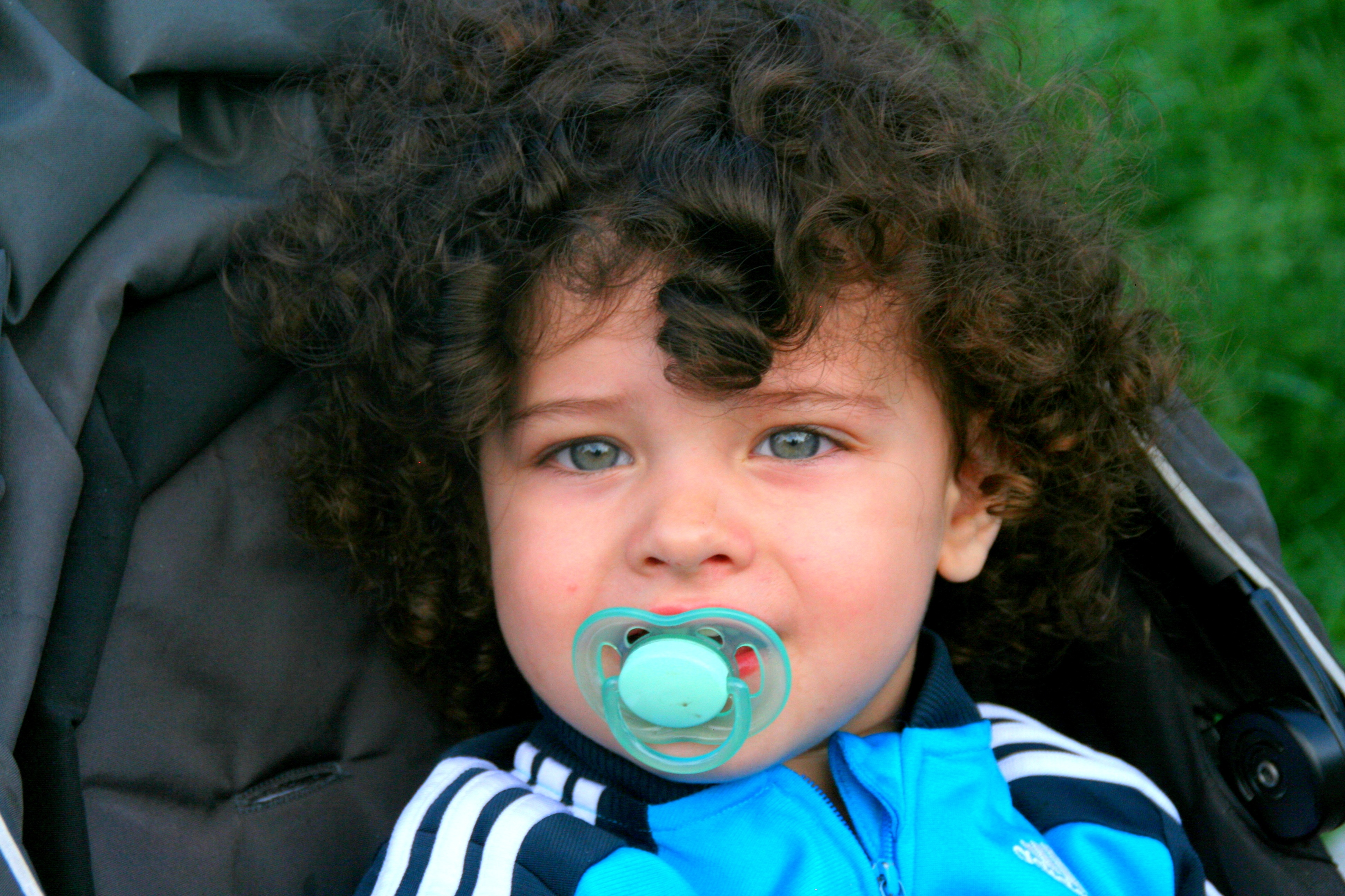 Curly Haired Blue Eyed Child With A Pacifier Free Image