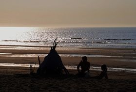 people near wigwam on the beach of the north sea
