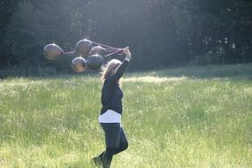 girl with black balloons running by meadow
