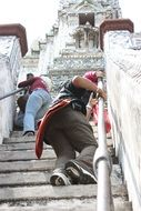 people climb the steep stairs of the temple