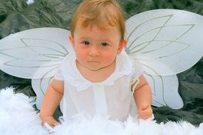 child in a white angel costume with wings