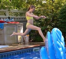girl jumps into the pool