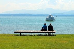 two persons sitting on wooden bench at calm water