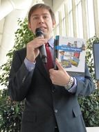 Lecturer with a microphone on a book presentation