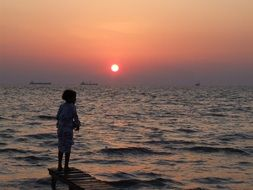 child on a pier near the ocean at sunset