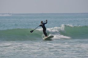 surfing with a paddle on the waves of the ocean in San Clemente, California