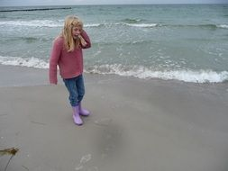 girl walking by the sea in rubber boots