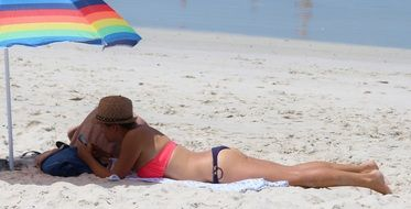 girl sunbathes on the beach under a multi-colored umbrella