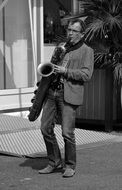 Black and white photo of Street Artist plays on a saxophone