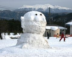 big snowman in view of mount kurai, japan