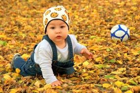 baby boy playing with a ball on a background of yellow autumn leaves
