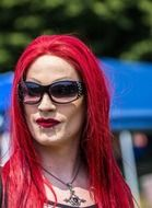 man with bright makeup and red hair at a gay parade