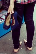 shoes with high heels in hand of barefeet girl