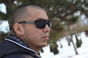 short-haired man in sunglasses against the background of a winter landscape