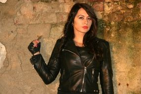 a seductive black-haired girl in a leather jacket with a knife in hand