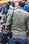 photographer with camera in crowd, back view