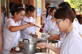 Women in white clothes give out food, Thailand