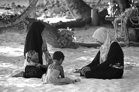 local people in the Maldives are resting on the sand