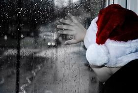 baby in Santa's hat looking out the rainy window