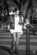 black and white photo of a girl walking down the street with iPod and earphones
