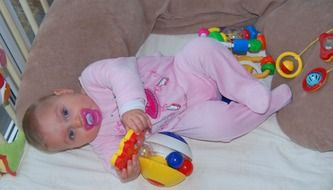 baby girl with pacifier in crib among toys
