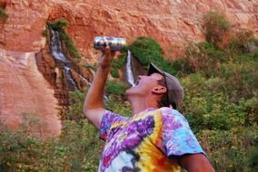man with a can of beer on the background of fresh water in the Grand Canyon