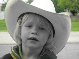 Black and white photo baby in a cowboy hat at colorful background with beautiful nature