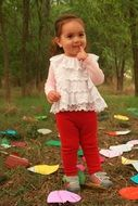 innocent girl among colorful papers in the garden