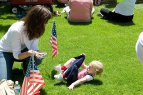 little girl with flag on green grass