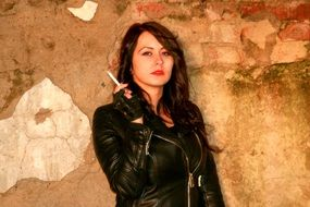 seductive girl in a leather jacket with a cigarette