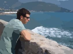man in sunglasses looks at the ocean